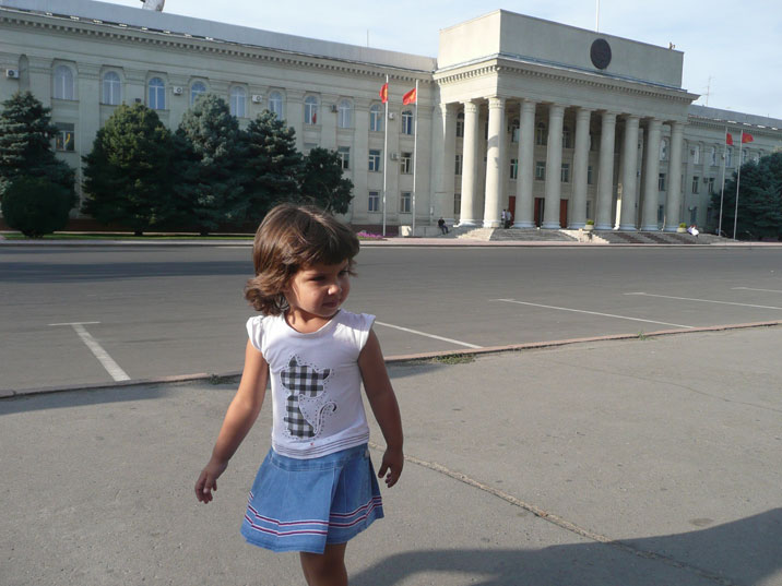 Little girl waling in front of the Kyrgyz parliament building