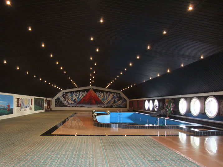 Large hall with a swimming pool and pictures on the walls