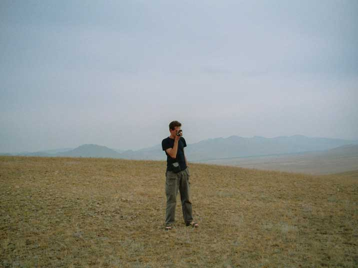 Comtourist cameraman shooting material on the Mongolian steppes