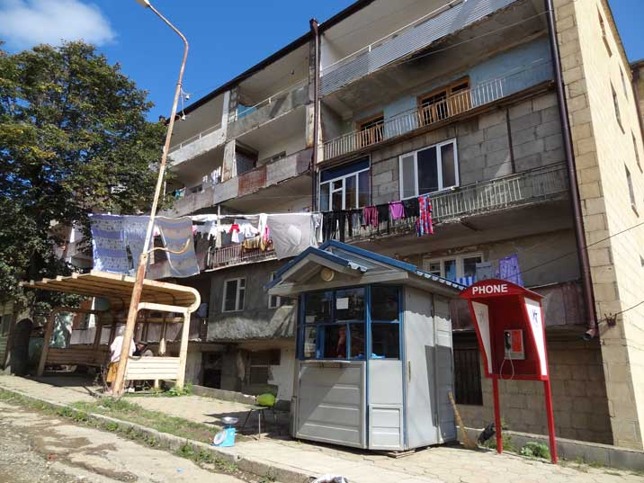 A housing block with a bus stop, pay phone and Kiosk in the town of Shushi in Nagorno-Karabakh
