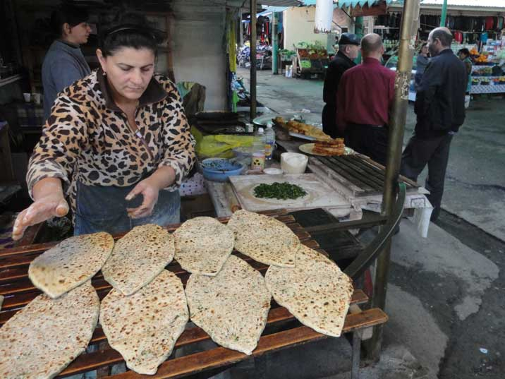 A lady on the Stepanakert Bazaar making Kutaby, a tasty pancake stuffed with herbs and greens