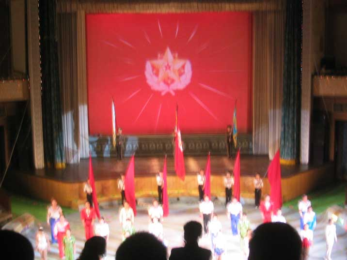 Army Circus acrobats with red flags in front of a big screen