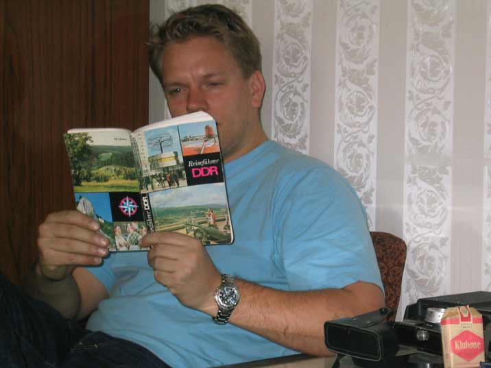 Comtourist editor reading the Reisefuhrer DDR, a tourist guidebook for the German Democratic Republic