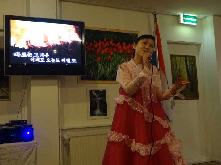 The performance is supported by a Karaoke system showing familiar North Korean propaganda images