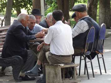 Old men playing backgammon and meanwhile discussing thing on the streets of Baku