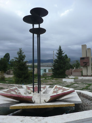 Concrete fountain and World War II monument with the names of local victims in the background