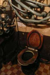 Toilet for the submarine officers with many water pipes overhead
