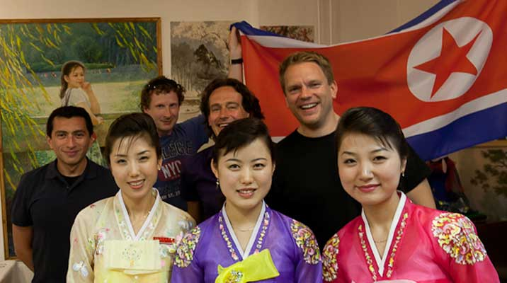 Our group posing for a photo with the friendly smiling North Korean waitresses and the North Korean flag in the background