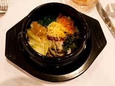 Famous Korean dish Bibimbap, meaning Mixed Meal served as a bowl of warm white rice topped with vegetables and gochujang