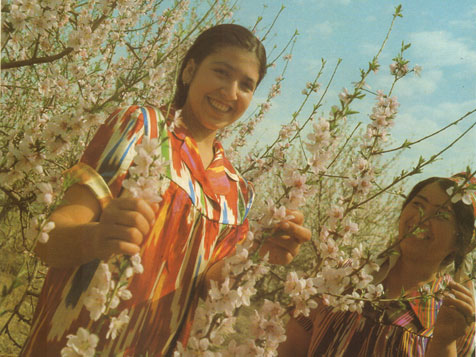 Smiling Tajik woman btween fruit trees from a Soviet era photobook