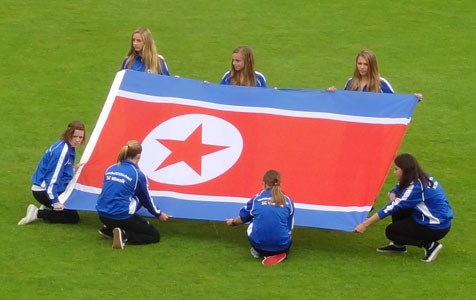 The North Korean womans football team hail the national flag before the football match against the Netherlands