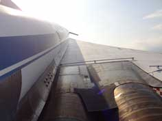 Right wing of the Tu-144 with the deployed canard at the end is the view from the rear access door